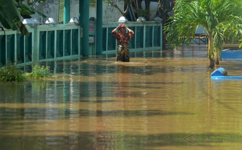 Seorang warga berjalan menembus banjir yang merendam kawasan Kraton, Pasuruan, Jawa Timur, Kamis (12/1/2017). Hujan yang turun beberapa hari terakhir dan meluapnya Sungai Welang merendam ratusan rumah di lima wilayah di kecamatan di Pasuruan.