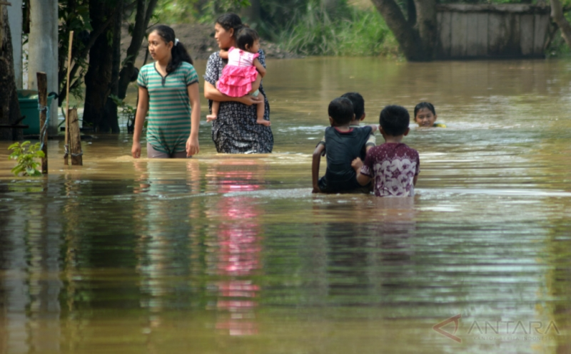 Sejumlah warga berjalan menembus banjir yang merendam kawasan Kraton, Pasuruan, Jawa Timur, Kamis (12/1/2017). Hujan yang turun beberapa hari terakhir dan meluapnya Sungai Welang merendam ratusan rumah di lima wilayah di kecamatan di Pasuruan.