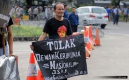 """Aktivis Jaringan Solidaritas Korban Untuk Keadilan (JSKK) membentangkan poster """"Tolak Dewan Kerukunan Nasional"""" saat aksi Kamisan ke-476 di depan Istana Merdeka, Jakarta, Kamis (12/1/2017). Aksi tersebut untuk meminta kepada Presiden Joko Widodo untuk menuntaskan kasus-kasus pelanggaran HAM yang pernah terjadi di Indonesia."""