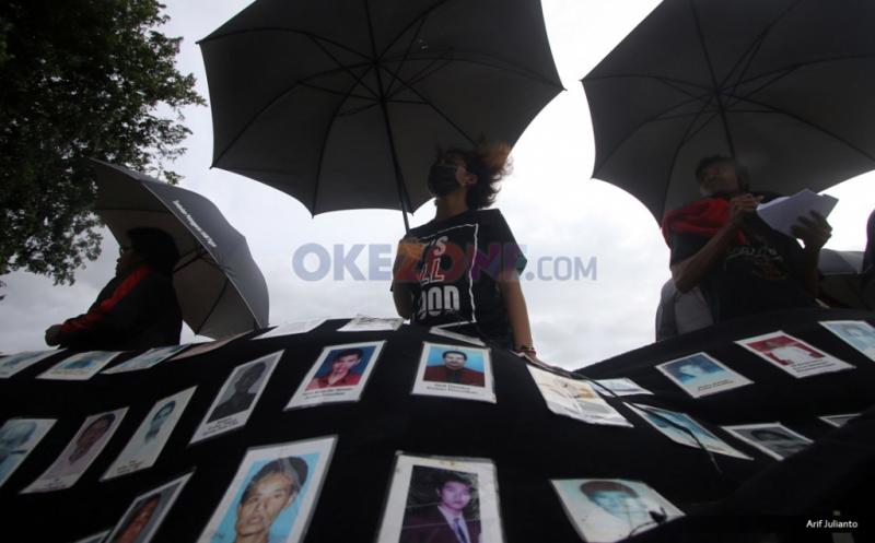 Aktivis Jaringan Solidaritas Korban Untuk Keadilan (JSKK) membentangkan kain hitam berisi foto diduga para korban kasus pelanggaran HAM, saat aksi Kamisan ke-476 di depan Istana Merdeka, Jakarta, Kamis (12/1/2017). Aksi tersebut untuk meminta kepada Presiden Joko Widodo untuk menuntaskan kasus-kasus pelanggaran HAM yang pernah terjadi di Indonesia.