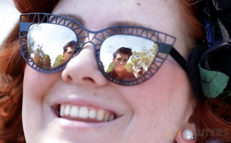 Refleksi pria bergaya seperti legendaris Elvis Presley terlihat di kacamata seorang perempuan dalam Festival Elvis di Paskes, Australia, Kamis (12/1/2017). Pada festival tersebut, penggemar meniru gaya berpakaian Raja Pop Elvis Presley.