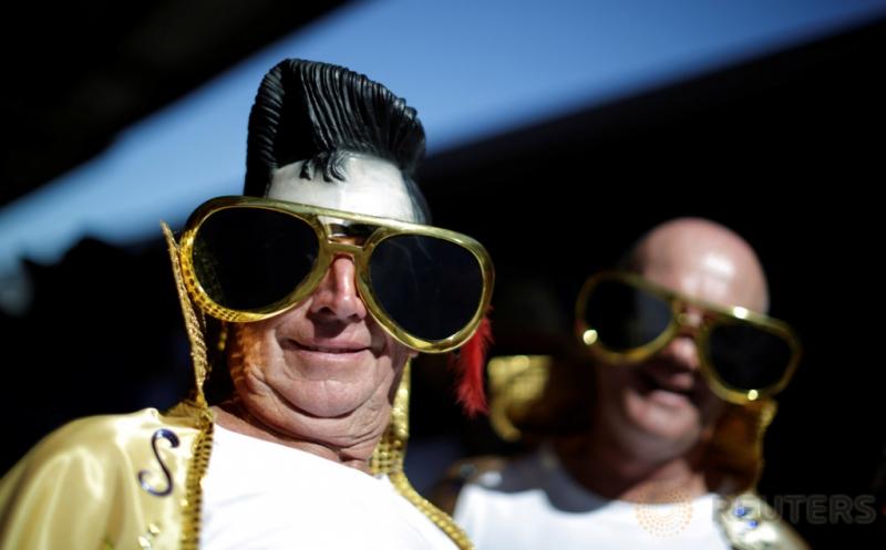 Dua pria bergaya seperti legendaris Elvis Presley terlihat di kacamata seorang perempuan dalam Festival Elvis di Paskes, Australia, Kamis (12/1/2017). Pada festival tersebut, penggemar meniru gaya berpakaian Raja Pop Elvis Presley.
