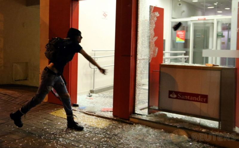 Demonstran melempari kaca sebuah gedung saat aksi unjuk rasa memprotes kenaikan tarif transportasi di Sao Paulo, Brasil, Kamis (12/1/2017). (REUTERS/Paulo Whitaker)