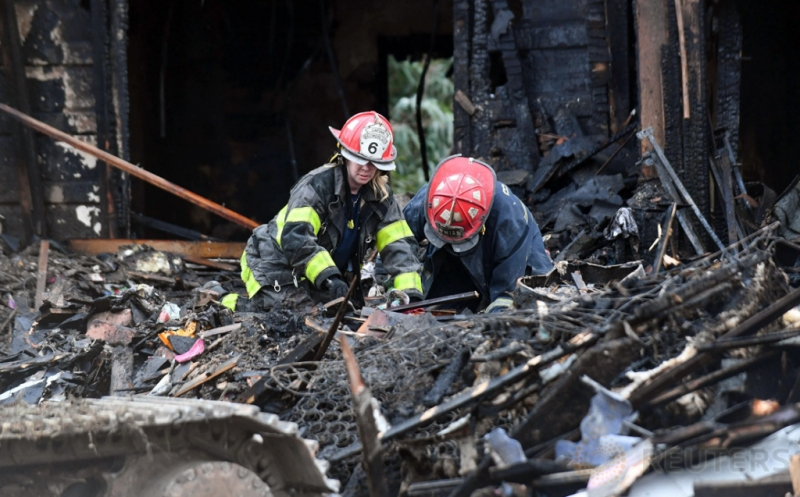 Dua petugas pemadam kebakaran berada di lokasi kebakaran sebuah rumah tiga lantai di Baltimore, Maryland, Amerika Serikat (AS), Kamis (12/1/2017). Sedikitnya enam anak tewas akibat kebakaran tersebut. (REUTERS/Bryan Woolston)