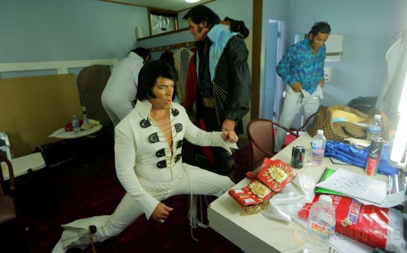 Seorang pria bergaya di depan cermin sebelum mengikuti kontes menyanyi pada Festival Elvis di Paskes, Australia, Jumat (13/1/2017). Pada festival tersebut, peserta diwajibkan meniru gaya berpakaian Raja Pop Elvis Presley.