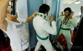 Seorang pria merias dirinya di depan cermin sebelum mengikuti kontes menyanyi pada Festival Elvis di Paskes, Australia, Jumat (13/1/2017). Pada festival tersebut, peserta diwajibkan meniru gaya berpakaian Raja Pop Elvis Presley.