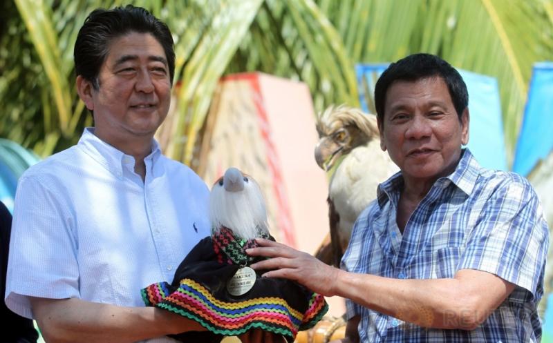 Presiden Filipina Rodrigo Duterte (kanan) menyerahkan boneka Elang Filipina bernama Sakura kepada Perdana Menteri Jepang Shinzo Abe di Davao, Filipina, Jumat (13/1/2017). Elang Filipina merupakan salah satu burung raptor hutan terbesar dan terkuat di dunia, serta termasuk elang terlangka di dunia. (REUTERS/Lean Daval Jr)