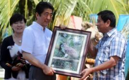 Presiden Filipina Rodrigo Duterte (kanan) menyerahkan bingkai foto Elang Filipina kepada Perdana Menteri Jepang Shinzo Abe di Davao, Filipina, Jumat (13/1/2017). Elang Filipina merupakan salah satu burung raptor hutan terbesar dan terkuat di dunia, serta termasuk elang terlangka di dunia. (REUTERS/Lean Daval Jr)