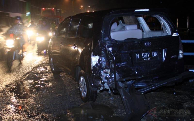 Pengendara sepeda motor melintas di sebuah mobil yang terlibat kecelakaan beruntun di Jalan Raya Purwodadi, Pasuruan, Jawa Timur, Jumat (13/1/2017). Kecelakaan beruntun tersebut melibatkan 11 kendaraan dan mengakibatkan empat orang tewas dan delapan orang luka-luka.