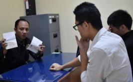 Petugas imigrasi menunjukkan paspor di depan dua warga negara Tiongkok, XW dan YL, saat akan dideportasi, di Kantor Imigrasi Madiun, Madiun, Jawa Timur, Sabtu (14/1/2017). Kantor Imigrasi Madiun mendeportasi dua orang warga negara Tiongkok karena melanggar dokumen keimigrasian.