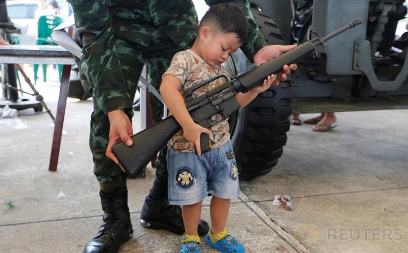 Tentara membantu seorang bocah dalam memegang senjata laras panjang pada perayaan Hari Anak di Bangkok, Thailand, Sabtu (14/1/2017). (REUTERS/Jorge Silva)