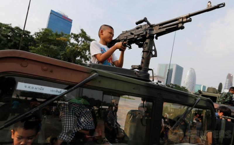 Seorang bocah memegang senjata laras panjang di atas kendaraan militer pada perayaan Hari Anak di Bangkok, Thailand, Sabtu (14/1/2017). Bak seorang tentara sungguhan, bocah ini terlihat serius dalam membidik sasaran dengan senjata laras panjang yang dipegangnya. (REUTERS/Jorge Silva)
