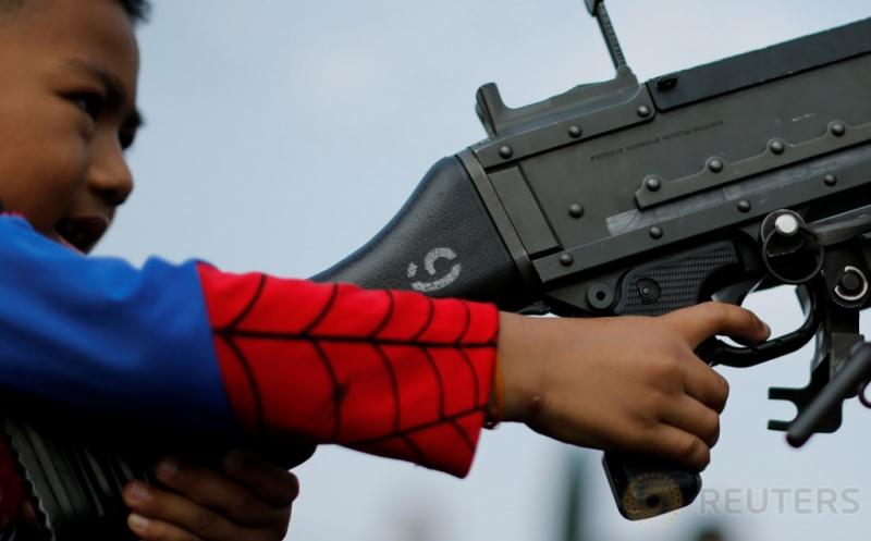 Seorang bocah memegang senjata laras panjang pada perayaan Hari Anak di Bangkok, Thailand, Sabtu (14/1/2017). Bak seorang tentara sungguhan, bocah ini terlihat serius dalam membidik sasaran dengan senjata laras panjang yang dipegangnya. (REUTERS/Jorge Silva)