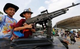 Dua anak berada di kendaraan militer saat perayaan Hari Anak di Bangkok, Thailand, Sabtu (14/1/2017). Kegiatan ini dapat menjadi edukasi bagi anak-anak untuk mengetahui bagaimana peran tentara saat berada di kendaraan militer. (REUTERS/Jorge Silva)