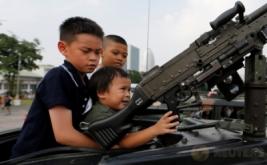 Tiga anak berada di kendaraan militer saat perayaan Hari Anak di Bangkok, Thailand, Sabtu (14/1/2017). Kegiatan ini dapat menjadi edukasi bagi anak-anak untuk mengetahui bagaimana peran tentara saat berada di kendaraan militer. (REUTERS/Jorge Silva)