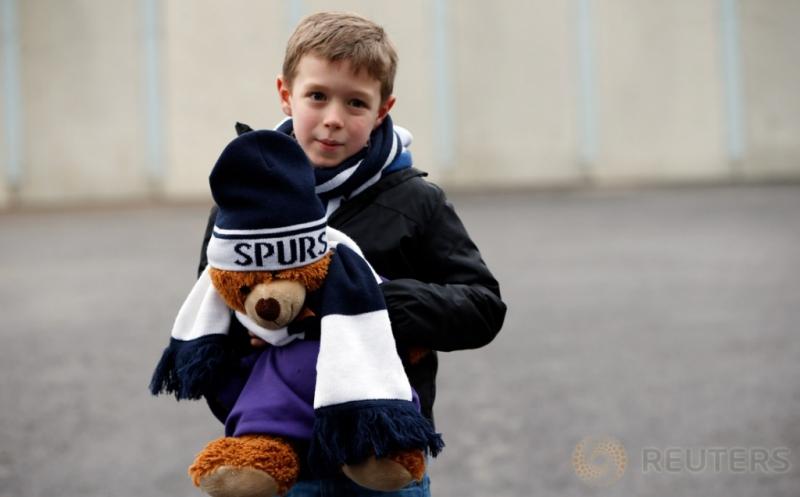 Seorang bocah membawa boneka beruang dengan penutup kepala bertuliskan Spurs saat mendatangi Stadion White Hart Lane untuk menyaksikan laga Spurs kontra West Bromwich Albion, Sabtu (14/1/2017). Bocah ini merupakan salah satu suporter setia Spurs. (Reuters/Paul Childs)