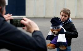 Seseorang mengabadikan bocah yang membawa boneka beruang dengan penutup kepala bertuliskan Spurs saat mendatangi Stadion White Hart Lane untuk menyaksikan laga Spurs kontra West Bromwich Albion, Sabtu (14/1/2017). Bocah ini merupakan salah satu suporter setia Spurs. (Reuters/Paul Childs)