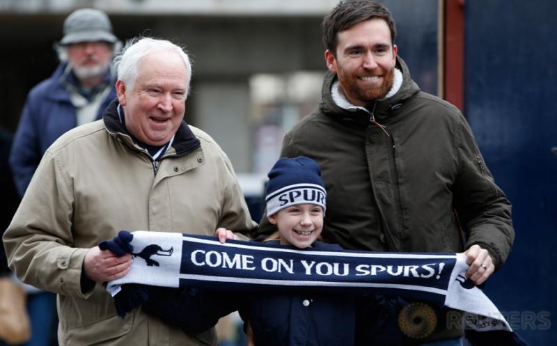 """Seorang bocah membentangkan syal bertuliskan """"Come On You Spurs!"""" saat bersama ayahnya untuk menyaksikan laga Spurs kontra West Bromwich Albion, Sabtu (14/1/2017). Bocah ini merupakan salah satu suporter setia Spurs. (Reuters/Paul Childs)"""