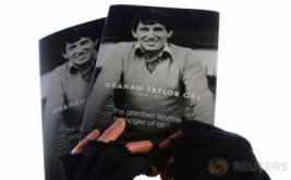 Seseorang memegang foto mantan Pelatih Timnas Inggris Graham Taylor. Graham Taylor yang meninggal dunia di usia 72 tahun pada Kamis (12/1) diduga karena serangan jantung. Selain pernah melatih timnas Inggris, Graham Taylor juga sempat melatih Watford dan Aston Villa.