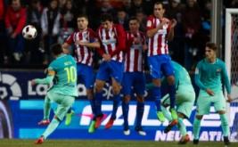 Lionel Messi (kiri) melakukan tendangan bebas ke arah gawang Atletico Madrid. (REUTERS/Sergio Perez)