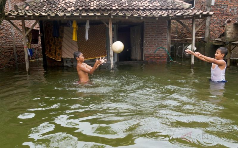Dua anak bermain di depan rumahnya yang terendam banjir di Sayung, Demak, Jawa Tengah, Rabu (15/2/2017). Banjir yang disebabkan luapan Sungai Dombo yang tak mampu menampung debit air akibat tingginya intensitas hujan tersebut merendam sekira 1.450 rumah warga dengan ketinggian air 30 cm-1 meter.