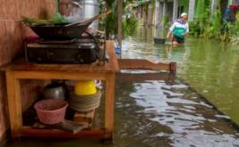 Seorang warga melewati genangan air yang membanjiri jalan di Sayung, Demak, Jawa Tengah, Rabu (15/2/2017). Banjir yang disebabkan luapan Sungai Dombo yang tak mampu menampung debit air akibat tingginya intensitas hujan tersebut merendam sekira 1.450 rumah warga dengan ketinggian air 30 cm-1 meter.