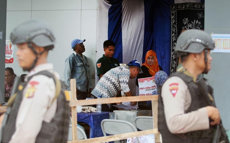 Petugas Polres Aceh Timur mengawasi proses perhitungan surat suara di Tempat Pemungutan Suara (TPS) Desa Tanoh Anoe, Kecamatan Idi Rayeuk, Aceh Timur, Aceh, Rabu (15/2/2017). Pengawasan dan pengamanan proses perhitungan suara dilakukan untuk kelancaran Pilkada serentak serta untuk mengantisipasi terjadinya keributan antar pendukung.