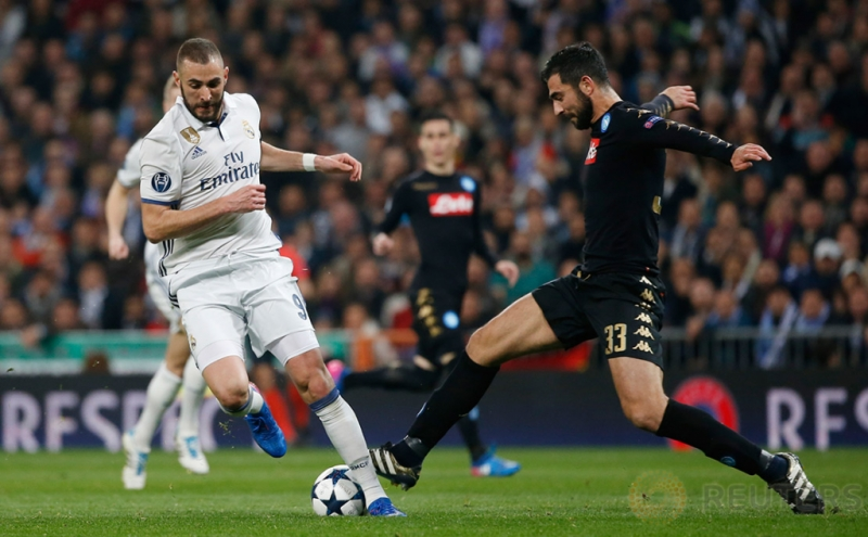 Karim Benzema saat berebut bola dengan Raul Albiol pada pertandingan 16 besar Liga Champions di Stadion Bernabeu. Reuters / Susana Vera