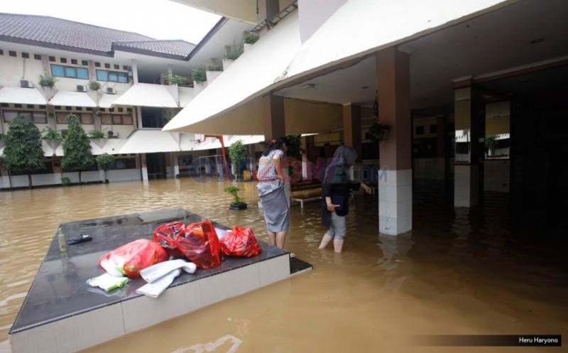 Sejumlah siswa melintasi halaman SMA Negeri 8 yang terendam banjir di Bukit Duri, Jakarta, Kamis (16/2/2017). Banjir yang merendam SMA ini membuat aktivitas belajar-mengajar terpaksa dihentikan.