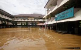 Seseorang melintasi halaman SMA Negeri 8 yang terendam banjir di Bukit Duri, Jakarta, Kamis (16/2/2017). Banjir yang merendam SMA ini membuat aktivitas belajar-mengajar terpaksa dihentikan.