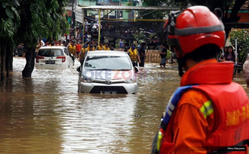 Petugas evakuasi berada di sebuah jalan yang terendam banjir di kawasan Bukit Duri, Jakarta, Kamis (16/2/2017). Banjir kiriman di kawasan ini terjadi sekira pukul 04.00 WIB dengan ketinggian air bervariasi.