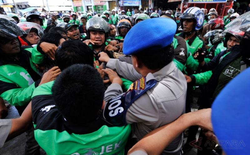 Puluhan pengemudi Go-Jek berusaha mendobrak pagar kantor Cabang Go-Jek Makassar, Jalan Bulukunyi, Sulawesi Selatan, saat berunjukrasa, Kamis (16/2/2017). Mereka menolak tarif baru yang diberlakukan manajemen khusus pelayanan Go Food atau layanan pengantaran makanan.