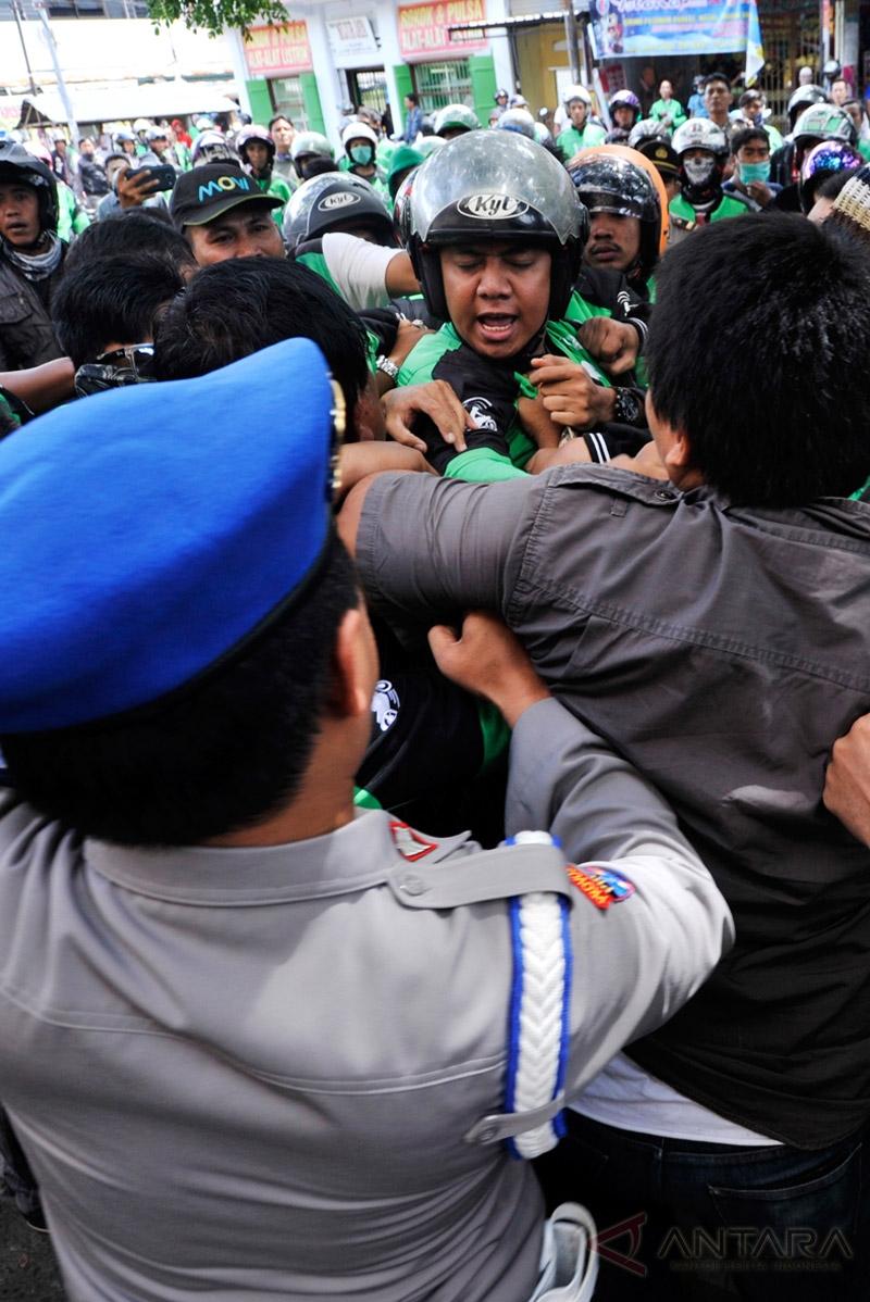 Puluhan pengemudi Go-Jek saling dorong dengan petugak kepolisian saat menggelar unjuk rasa di kantor Cabang Go-Jek Makassar, Jalan Bulukunyi, Sulawesi Selatan, Kamis (16/2/2017). Mereka menolak tarif baru yang diberlakukan manajemen khusus pelayanan Go Food atau layanan pengantaran makanan.