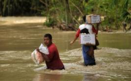 Sejumlah warga menerjang banjir saat membawa bantuan makanan di Desa Jatibogor, Kabupaten Tegal, Jawa Tengah, Kamis (16/2/2017). Banjir setinggi 50 cm - satu meter tersebut mengakibatkan 300 jiwa warga yang berada di desa itu terisolir, sehingga aktivitas warga terganggu.
