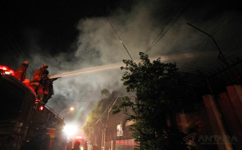 Petugas PMK berusaha memadamkan gudang yang terbakar di Jalan Pesapen Kali, Surabaya, Jawa Timur, Rabu (15/2/2017) malam. Sebanyak sepuluh unit mobil pemadam kebakaran dikerahkan untuk memadamkan kebakaran gudang tempat penyimpanan kertas bungkus rokok tersebut.