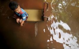 Seorang anak duduk di atas meja saat banjir melanda Kelurahan Sidakaton, Tegal, Jawa Tengah, Kamis (16/2/2017). Meluapnya Sungai Kaligangsa karena hujan deras mengakibatkan sedikitnya 3.400 rumah warga yang berada di pinggir Pantura terendam banjir setinggi 30 centimeter hingga 1,5 meter.