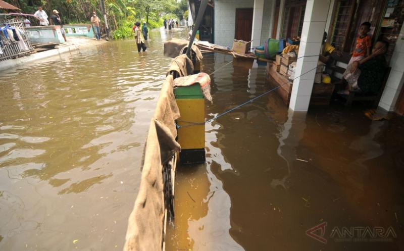 Sejumlah warga duduk di teras rumahnya yang tergenang banjir di Kelurahan Sidakaton, Tegal, Jawa Tengah, Kamis (16/2/2017). Meluapnya Sungai Kaligangsa karena hujan deras mengakibatkan sedikitnya 3.400 rumah warga yang berada di pinggir Pantura terendam banjir setinggi 30 centimeter hingga 1,5 meter.
