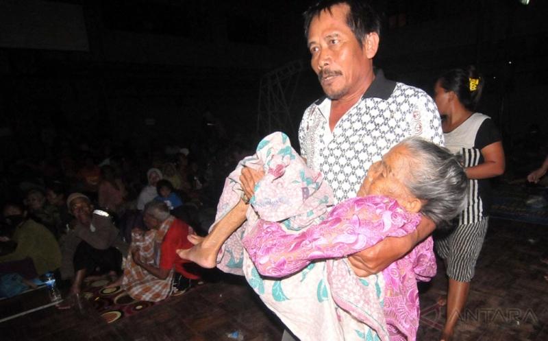 Seorang warga membawa lansia korban banjir saat mengungsi di GOR Sasana Krida Adhuikarsa, Brebes, Jawa Tengah, Kamis (16/2/2017). Dua lansia korban banjir terpaksa dibawa ke rumah sakit akibat kondisinya semakin parah akibat mengalami kedinginan.