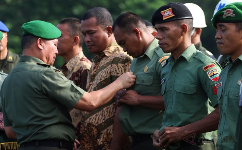 Kasdam I/Bukit Barisan Brigjen TNI Tiopan Aritonang (kiri) menanggalkan seragam anggota TNI pada upacara pemberhentian tidak dengan hormat (PTDH), di Medan, Sumatera Utara, Jumat (17/2/2017). Sebanyak 21 prajurit TNI Kodam I/Bukit Barisan dipecat, diantaranya terlibat narkoba dan desersi.