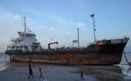 Warga melintasi kapal tanker Atlantic 33 yang terdampar di Pantai Nongsa, Batam, Kepulauan Riau, Jumat (17/2/2017). Kapal tanker Atlantic 33 yang belum diketahui pemiliknya tersebut terdampar di Pantai Nongsa, Batam karena terbawa arus ketika terjadi pasang dan angin yang kuat pada Rabu 15 Februari 2017 lalu.