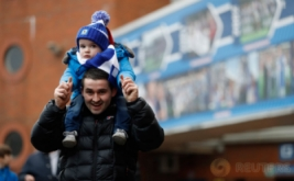 Seorang warga membawa anak kecil saat akan menyaksikan laga 16 besar Piala FA yang mempertemukan tuan rumah Blackburn Rovers dengan Manchester United. Pada laga tersebut, Blackburn Rovers menelan kekalahan 1-2 dari United. (Reuters/Carl Recine)