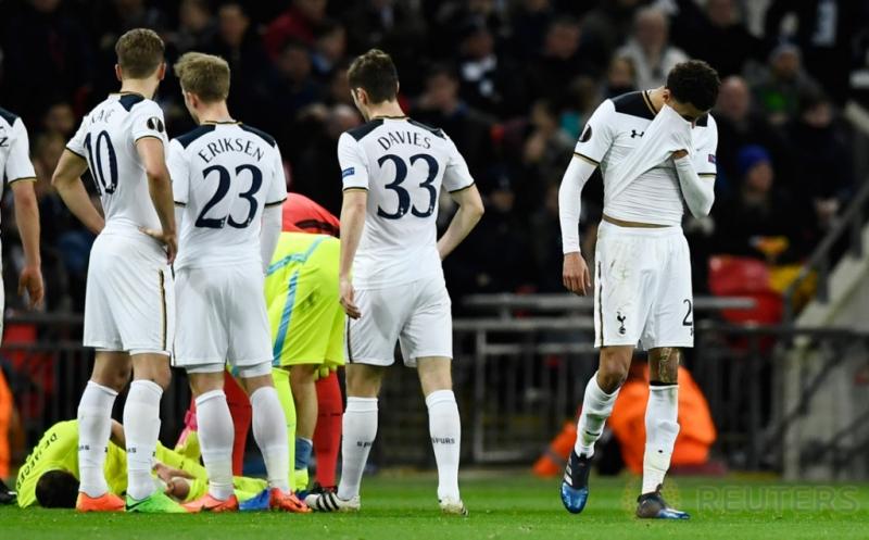 Gelandang Tottenham Hotspur, Dele Alli (kanan) berjalan sambil menutupi sebagian wajahnya usai diganjar kartu merah setelah melakukan tekel keras terhadap pemain KAA Gent, Brecht Dajaegere, pada laga Liga Europa di Stadion Wembley, Jumat (24/2/2017) dini hari WIB. (Reuters/Dylan Martinez)