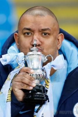 "Suporter Manchester City mencium ""trofi"" FA Cup sebelum pertandingan Manchester City kontra Huddersfield pada putaran kelima Piala FA di Stadion Etihad, Manchester, Inggris, Kamis (2/3/2017) dini hari WIB. (Reuters/Jason Cairnduff)"