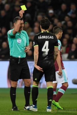 Wasit Andre Marriner (kiri) memberikan kartu kuning kepada Cesc Fabregas. (Reuters/Toby Melville)