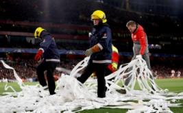 Petugas membersihkan tisu yang dilempar suporter Bayern Munich pada leg kedua babak 16 besar Liga Champions di Stadion Emirates, London, Inggris, Rabu (8/3/2017) dini hari WIB. (Reuters/Stefan Wermuth)