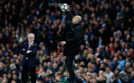 Pelatih Stoke City Mark Hughes (kiri) menyaksikan pelatih Manchester City Pep Guardiola yang sedang menangkap bola di pinggir lapangan. (Reuters/Phil Noble)