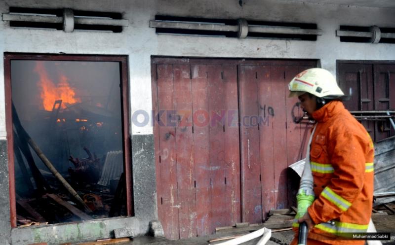 Petugas berusaha memadamkan api yang membakar sebuah pemukiman  yang terbakar di Kramat Bunder, Senen, Jakarta Pusat, Minggu, (19/3/2017). Kebakaran diduga dari hubungan listrik arus pendek di minimarket tersebut.