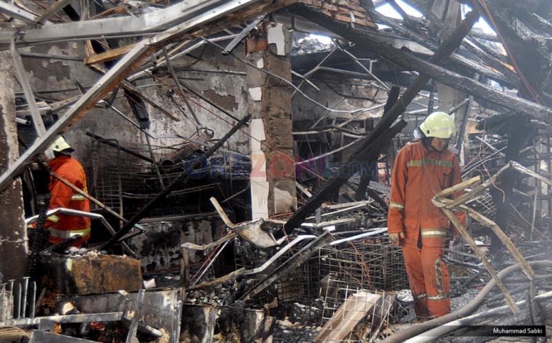 Petugas berusaha memadamkan api yang membakar minimarket  yang terbakar di Kramat Bunder, Senen, Jakarta Pusat, Minggu, (19/3/2017). Kebakaran diduga dari hubungan listrik arus pendek di minimarket tersebut.