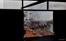 Petugas dan warga berusaha memadamkan api yang membakar sebuah pemukiman dan minimarket  yang terbakar di Kramat Bunder, Senen, Jakarta Pusat, Minggu, (19/3/2017). Kebakaran diduga dari hubungan listrik arus pendek di minimarket tersebut.