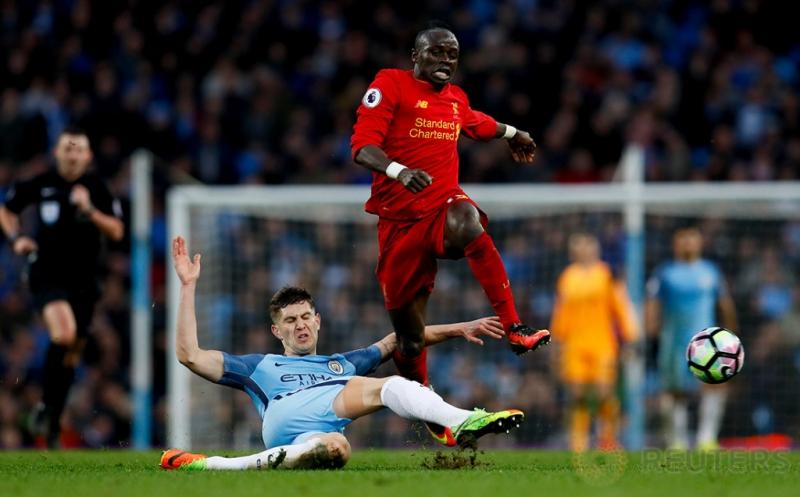 Pemain Manchester City John Stones (kiri) merebut bola dari kaki Sadio Mane pada laga lanjutan Liga Inggris 2016-2017 di Etihad Stadium, Senin (20/3/2017) dini hari WIB. Manchester City harus puas berbagi poin dengan Liverpool setelah kedua tim bermain imbang 1-1. (Reuters/Jason Cairnduff)